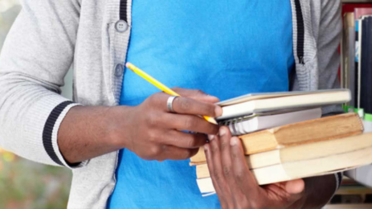 Crop of the hands and mid-section of young male student holding a pencil and some books, with a bookshelf in the background.