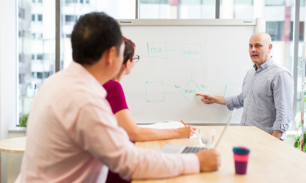 Man at whiteboard showing two other people how something works by pointing to diagram.